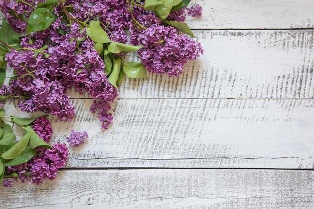 Frame van paarse lila bloemen met ruimte voor tekst op witte vintage houten bord.