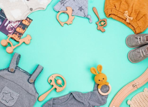 Frame van pasgeboren babykleertjes, houten zitzak, bijtring en speelgoed