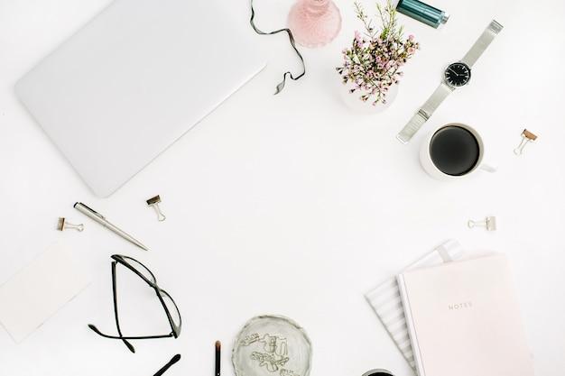 Frame van pastelroze notitieboekje, laptop, bril, koffiekopje, wilde bloemen en accessoires op wit bureau. platliggend, bovenaanzicht