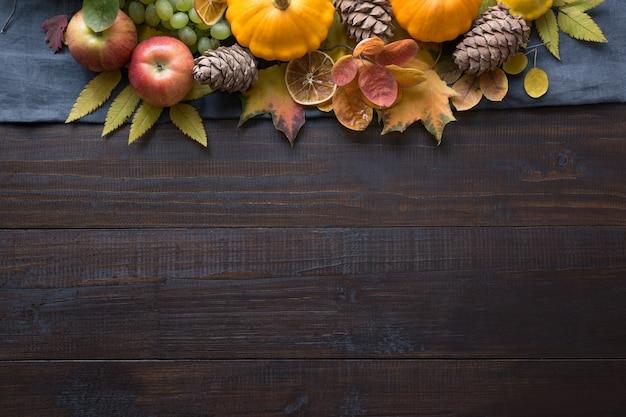 Frame van pompoen en esdoorn bladeren op een houten bord. bovenaanzicht