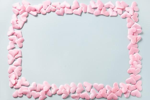 Frame van romantische roze harten op blauwe achtergrond. valentijnsdag wenskaart met kopie ruimte. liefde concept.
