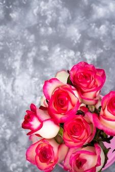 Frame van rood wit roze bloemboeket op stenen tafel.
