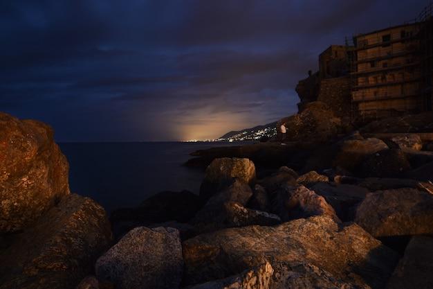 Frame van rotsen op de voorgrond verre uitzicht op de stad genua
