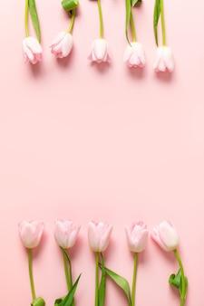 Frame van roze tulpen op een roze achtergrond.