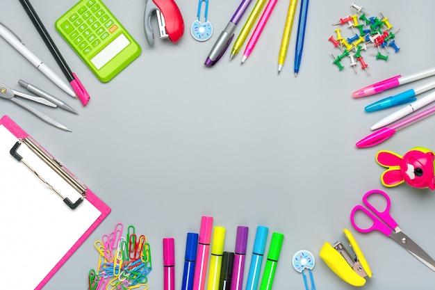 Frame van school- en kantoorbenodigdheden paperclips, schaar, pennen, viltstiften, puntenslijper, rekenmachine, nietmachine geïsoleerd op grijze achtergrond plat lag bovenaanzicht terug naar school concept
