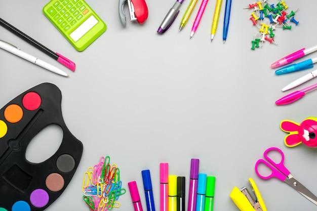 Frame van school- en kantoorbenodigdheden paperclips, schaar, pennen, viltstiften, puntenslijper, rekenmachine, nietmachine geïsoleerd op grijze achtergrond plat leggen
