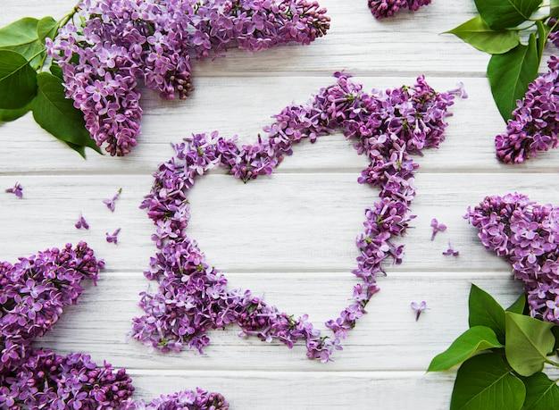 Frame van takken en bloemen van lila in de vorm van een hart