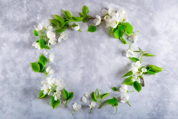 Frame van takken van een witte bloeiende appelboom op een lichtgrijze bovenaanzicht als achtergrond