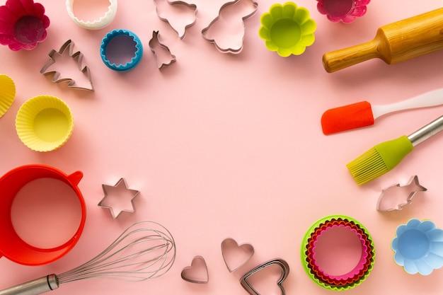 Frame van verschillende bakselwerktuigen op roze achtergrond. ruimte voor tekst.