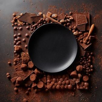 Frame van verschillende chocolaatjes en cacaopoeder met zwarte plaat voor de tekst op een donkere achtergrond
