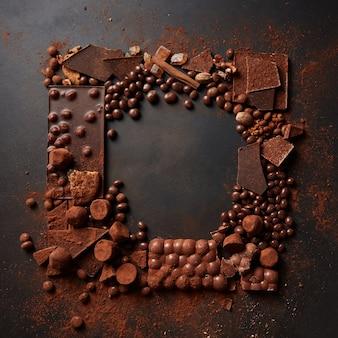 Frame van verschillende chocolaatjes en cacaopoeder op een donkere achtergrond