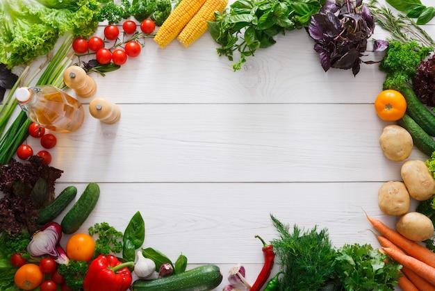 Frame van verse groenten op wit hout met kopie ruimte