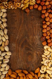 Frame van verspreide geassorteerde noten op een houten tafel. kopieer ruimte.