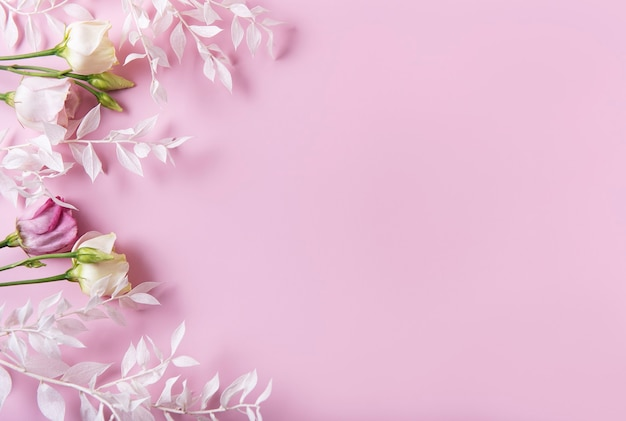 Frame van witte takken met bladeren en bloemen op een roze achtergrond