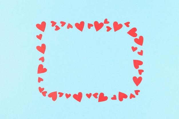 Frame voor inscripties uit rood uitgesneden en papieren hartjes op een blauwe achtergrond
