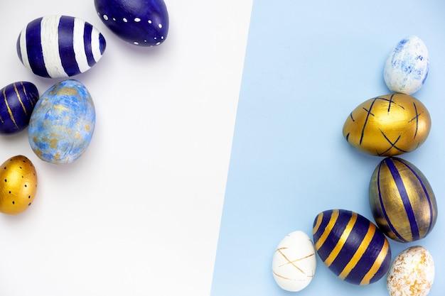 Frame voor tekst gemaakt van paaseieren blauw, wit en goudkleurig op blauw