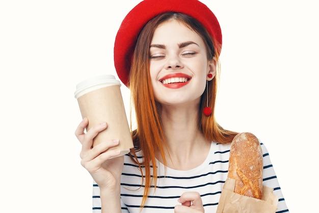 Française in een rode hoed met een kopje koffie en een blauwe achtergrond