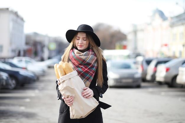 Française met baguettes in de tas op weg naar buiten de winkel