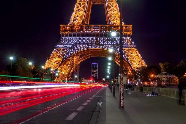 Frankrijk. nacht aan de voet van de eiffeltoren. zwaar verkeer en mensen op de jena-brug