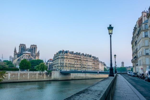 Frankrijk. vroege zomerochtend aan de oever van de rivier de seine en de renovatie van de notre dame na de brand van 2019. geparkeerde auto's en motoren