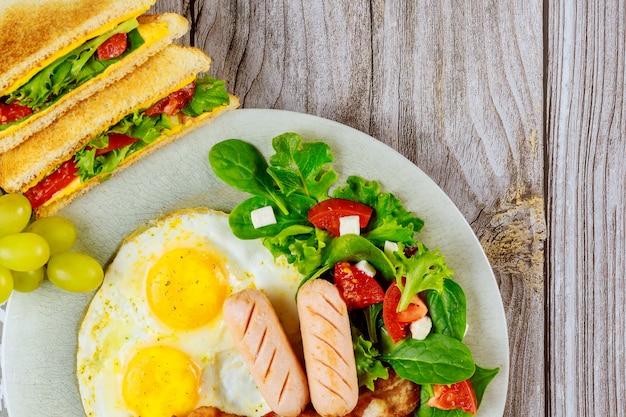 Franks, gebakken eieren, sandwiches met gegrilde kaas en salade als ontbijt.