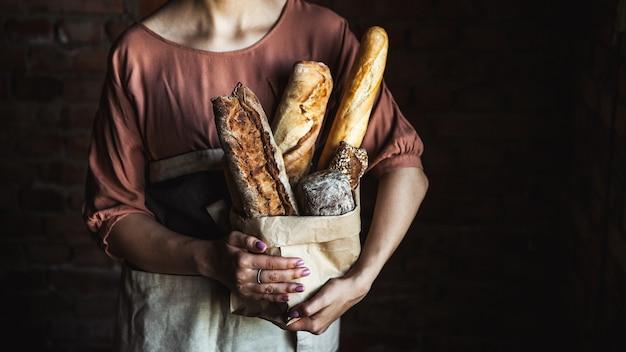 Frans stokbrood in vrouwelijke handen op een zwarte achtergrond. zelfgemaakt bakken