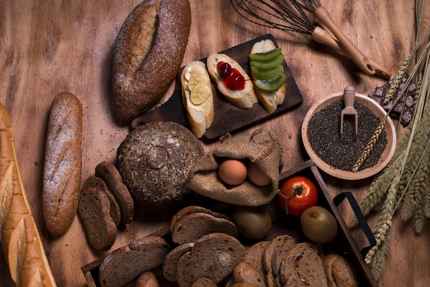 Frans stokbrood, kersensaus, banaan, tarwezemelen, chocolaatjes, zaad en bloem op hout.