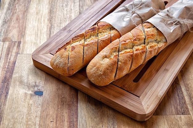 Frans stokbrood verpakt in inpakpapier op een snijplank. houten achtergrond.