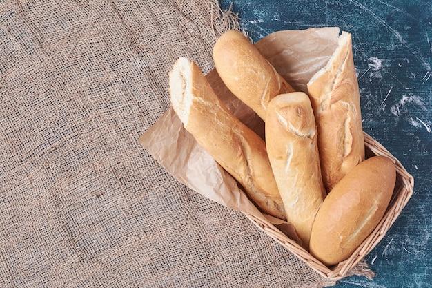 Franse baguettes in een mand op blauwe tafel.