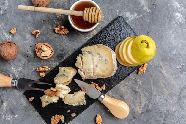 Franse blauwe kaas roquefort, gemaakt van schapenmelk met walnotenhoning en peer. banner, menu, receptplaats voor tekst, bovenaanzicht.