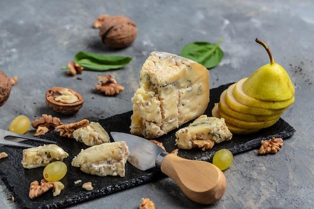Franse blauwe kaas roquefort, gemaakt van schapenmelk met walnotenhoning en peer. bovenaanzicht.