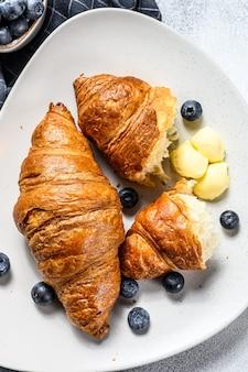 Franse boterachtige croissants met bosbessen op een bord. grijze achtergrond. bovenaanzicht.