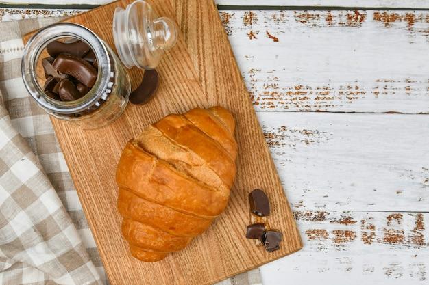 Franse chocolade croissants bovenaanzicht. het begin van de ochtend. verse franse croissant. koffiekopje en vers gebakken croissants op een houten. .