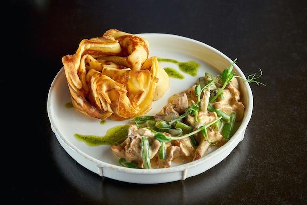 Franse crêpe met cantharellen in een romige saus en pestosaus. ontbijt. selectieve aandacht