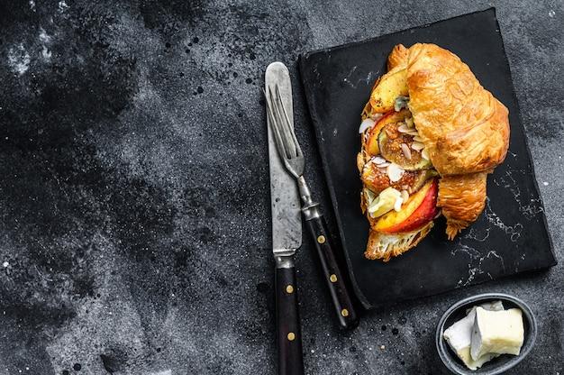 Franse croissant met bree-kaas, perzik en vijgen. zwarte houten achtergrond. bovenaanzicht. kopieer ruimte.