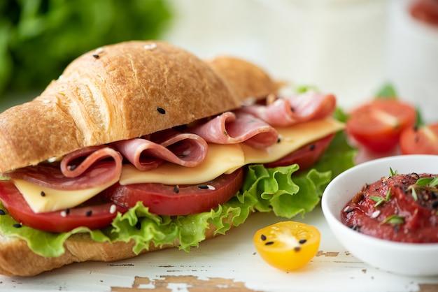 Franse croissant met ham, kaas, tomaat en salade