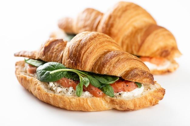 Franse croissant met zalm, roomkaas en spinazie op een witte achtergrond, selectieve aandacht