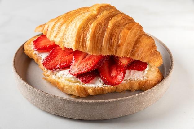 Franse croissantsandwich met verse rijpe aardbeien en roomkaas in een plaat op wit marmeren oppervlak