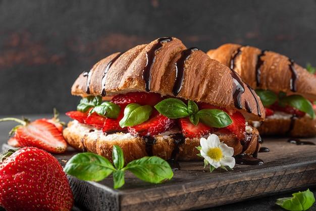 Franse croissantsandwiches met verse aardbeien, roomkaas, basilicum en chocoladesaus op donkere ondergrond