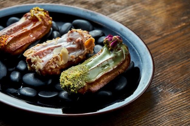 Franse eclairs met banketbakkersroom en diverse toppings geserveerd op een zwarte plaat op een houten achtergrond. restaurant eten.