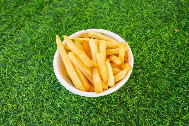 Franse frietjes geel op groen gras, bovenaanzicht close-up.