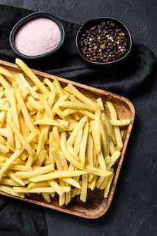 Franse frietjes in een houten kom. biologische aardappelen. zwarte achtergrond. bovenaanzicht.