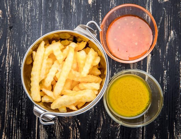 Franse frietjes met ketchup op houten oppervlak.