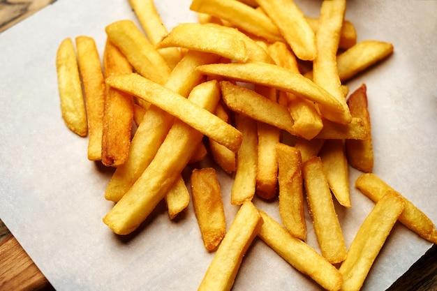 Franse frietjes op wit papier achtergrond, close-up. frisse en knapperige frietjes