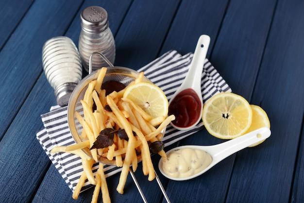 Franse gebakken aardappelen in metalen vergiet met saus op houten oppervlak