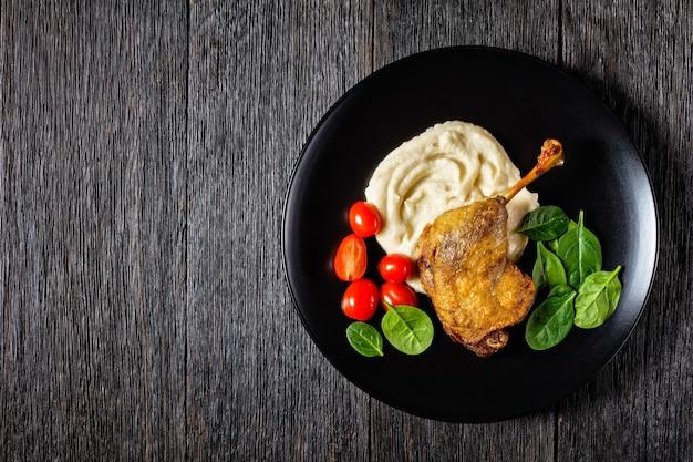 Franse keuken geroosterde eendenpoot - gekonfijte eend met pastinaakpuree en sinaasappelsaus, met verse spinaziebladeren geserveerd op een witte plaat op een donkere houten achtergrond, bovenaanzicht, kopieerruimte