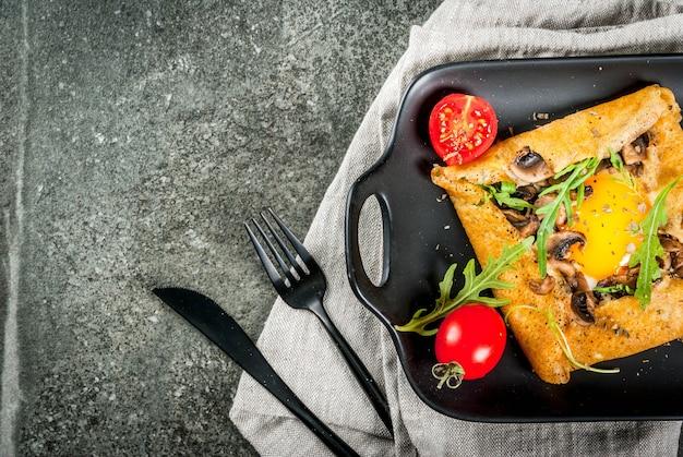 Franse keuken ontbijt lunch snacks veganistisch eten traditioneel gerecht galette sarrasin pannenkoeken met eieren kaas gebakken champignons rucola bladeren en tomaten op zwarte stenen tafel