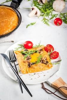 Franse keuken. ontbijt, lunch, snacks. veganistisch eten. traditionele schotel galette sarrasin. pannenkoeken met eieren, kaas, gebakken champignons, rucola bladeren en tomaten. op een witte betonnen tafel.