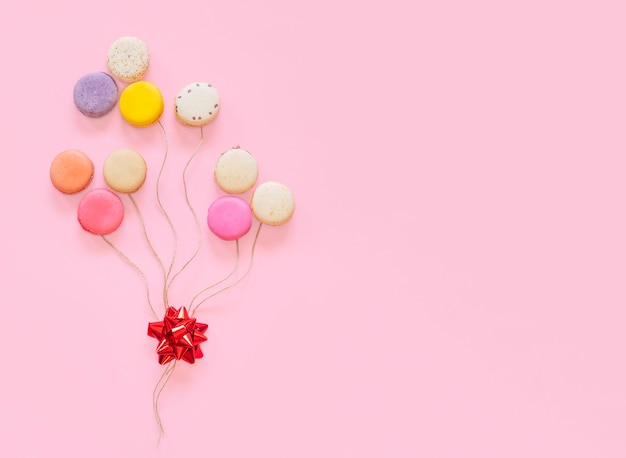 Franse kleurrijke makaronscakes in vorm van ballons die op roze achtergrond worden geïsoleerd.