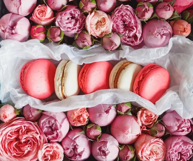 Franse macaroncake. bitterkoekjes in doos met verse bloemen. bovenaanzicht.